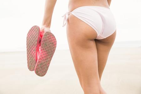 flip flops: Fit woman in bikini holding flip flops at the beach