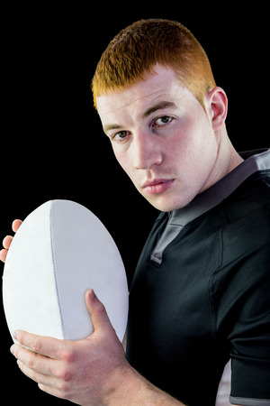 profile view: Profile view of a rugby player holding a rugby ball