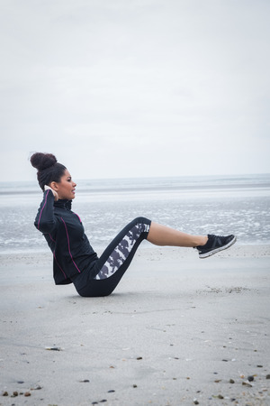girl working out: Fit girl working out on cold day at the beach