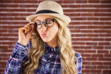air kiss: Gorgeous blonde hipster sending air kiss against red brick background Stock Photo