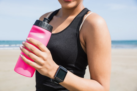 water bottles: Fit woman wearing smart watch at the beach Stock Photo