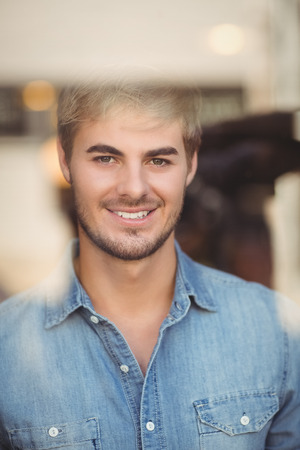 looking through: Portrait of smiling hipster looking through window at coffee shop Stock Photo