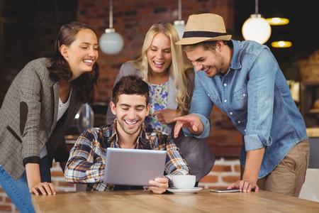 커피 숍에서 태블릿 컴퓨터를보고 웃는 친구 스톡 콘텐츠 - 42430510