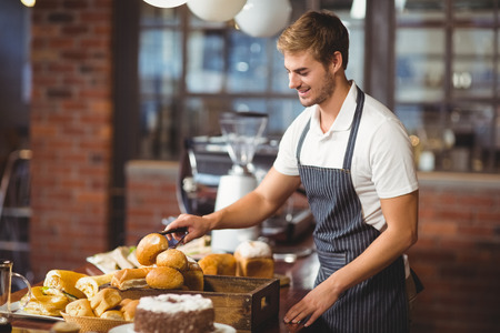 waiter: Handsome waiter picking up a roll at the coffee shop
