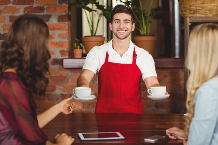Portrait of a waiter serving coffees to customers at the coffee shop Stock Photo - 42430627