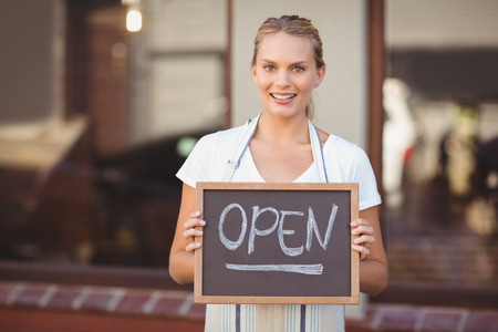 open sign: Portrait of smiling waitress showing chalkboard with open sign at coffee shop Stock Photo
