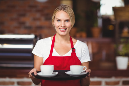 coffees: Portrait of a waitress holding a tray with coffees at the coffee shop