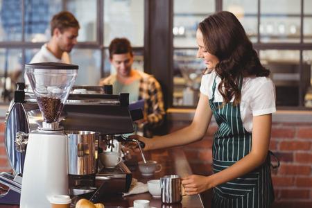 かなりバリスタのコーヒー ショップでコーヒーのカップを作る 写真素材