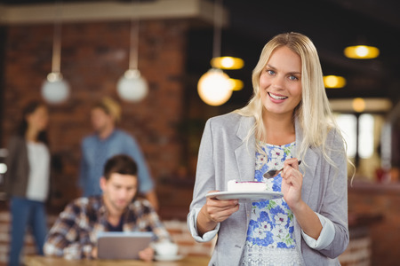 woman eating cake: Portrait of smiling blonde woman eating cake in front of her friends at coffee shop