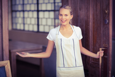welcome smile: Portrait of smiling blonde waitress welcoming at coffee shop