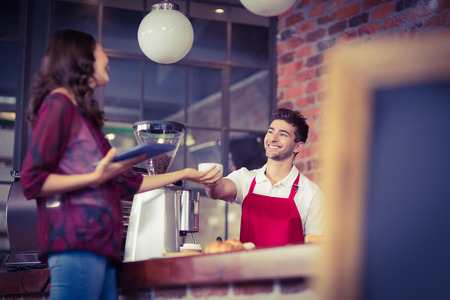 customer: Smiling waiter serving a client at the coffee shop