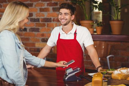 meseros: Cliente bonita que hace un pago móvil en la tienda de café Foto de archivo