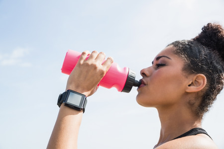 human wrist: Fit woman wearing smart watch and drinking at the beach Stock Photo