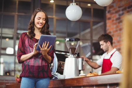 Mooie vrouw met behulp van haar tablet in de koffieshop Stockfoto