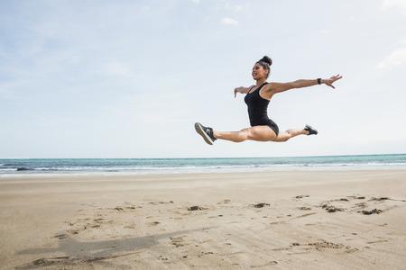 bailarina de ballet: Ajustar la mujer saltando en la arena en la playa