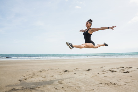 ballet dancer: Fit woman leaping on the sand at the beach