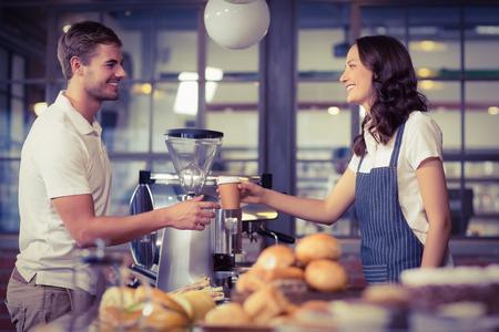 Bastante barista sonriendo servir a un cliente en la tienda de café Foto de archivo