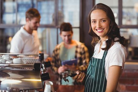 servicio al cliente: Retrato de un barista hacer una taza de café en la cafetería