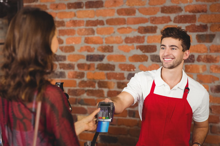 waiter: Smiling waiter handing a pin terminal at the coffee shop Stock Photo