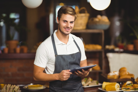 cafeterias: Portrait of a handsome waiter holding a tablet at the coffee shop Stock Photo