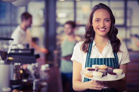 waitress: Portrait of a waitress showing a plate of cupcakes at the coffee shop