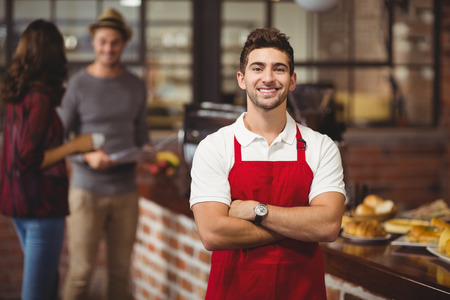 mandil: Retrato de un camarero con los brazos cruzados en la cafetería Foto de archivo