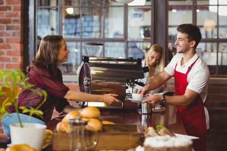 A smiling barista serving a client at the coffee shop Stok Fotoğraf