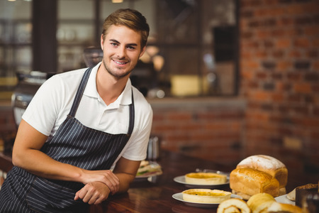 food shop: Portrait of a handsome waiter leaning on a food table at coffee shop