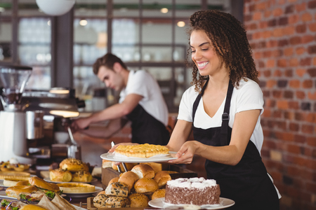 waitress: Smiling waitress holding cake in front of colleague at coffee shop
