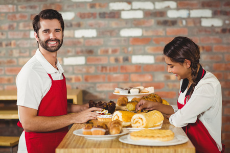 tidying up: Portrait of waiters tidying up pastries on the counter at the coffee shop