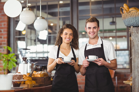 waitress: Portrait of smiling waiter and waitress holding cup of coffee at coffee shop