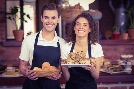 waiter: Portrait of smiling waiter and waitress holding bread bun at coffee shop