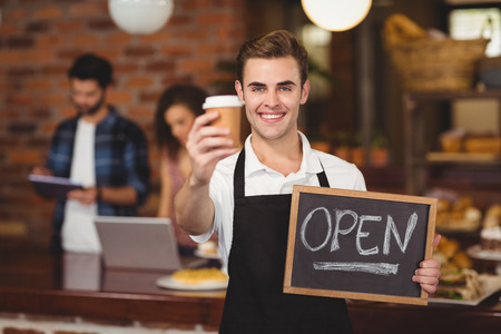 Portrait of smiling barista holding take-away cup and open sign at coffee shop