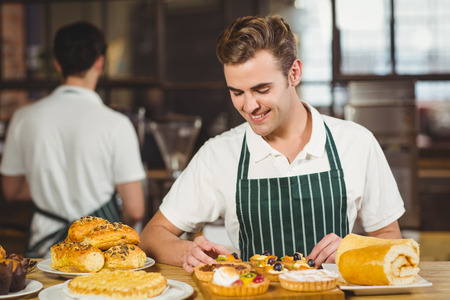 tidying up: Smiling waiter tidying up the pastries at the coffee shop Stock Photo