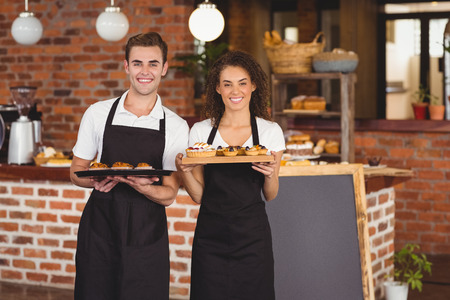 waitress: Portrait of smiling waiter and waitress holding tray with muffins at coffee shop Stock Photo