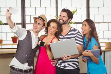 grimacing: Grimacing friends taking selfies at coffee shop Stock Photo