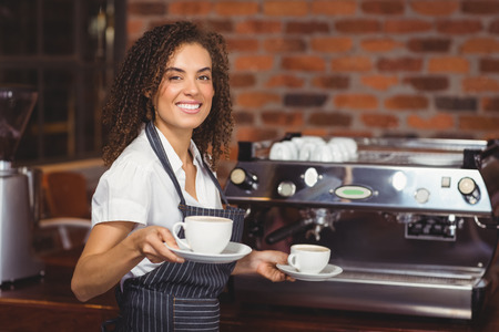 cafe shop: Portrait of smiling barista holding two cups of coffee at coffee shop