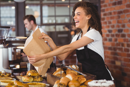 Smiling waitress giving paper bag to customer at coffee shop Foto de archivo
