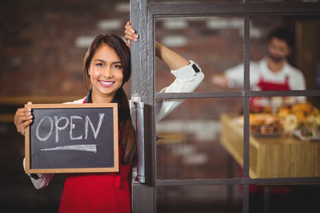 barista: Portrait of waitress showing chalkboard with open sign at coffee shop Stock Photo