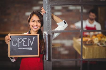 abrir puertas: Retrato de camarera mostrando pizarra con la muestra abierta en la cafeter�a Foto de archivo