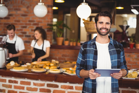 Portrait of smiling hipster using tablet in front of working barista at coffee shop