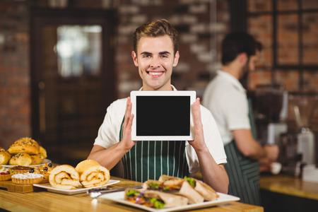 meseros: Retrato de un camarero que sostiene una tableta digital en la cafetería