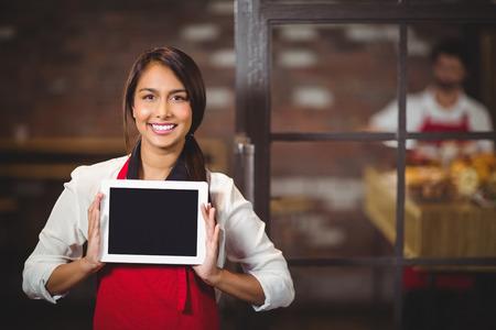 mujer trabajadora: Retrato de una camarera que muestra una tableta digital en la tienda de caf�