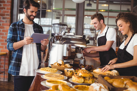 waiter: Smiling colleagues serving customer with tablet at coffee shop