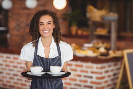 Portret van barista met een dienblad met kopjes koffie in de koffieshop Stockfoto