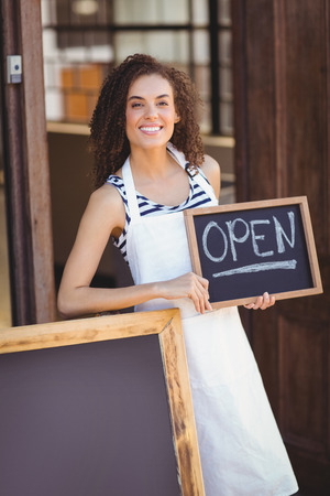 open: Portrait of waitress showing chalkboard with open sign at coffee shop Stock Photo