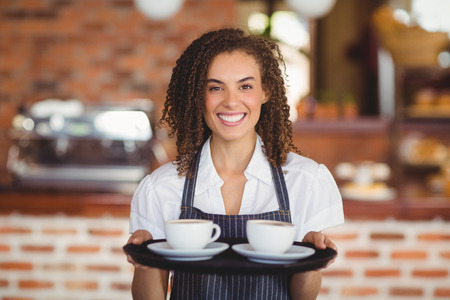 waitress: Portrait of barista holding a tray of coffee cups at the coffee shop