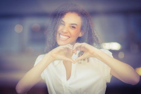 haciendo el amor: Retrato de una mujer que hace la forma del corazón en la cafetería Foto de archivo