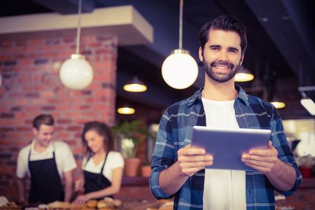 커피 가게에서 작업 바리의 앞에 태블릿을 사용하여 웃는 hipster의 초상화