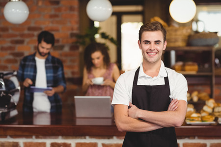 Portrait of smiling barista with arms crossed in front of customers at coffee shop
